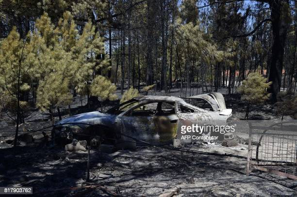 The burnt out carcass of a vehicle is pictured following a wildfire in the village of Vila Cha near Alijo on July 18 2017 A month after the deadliest...