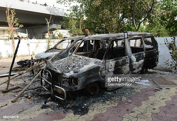 The burntout remains of vehicles after violent protests are seen inside near the Ahmedabad Municipal Corporation office in Ahmedabad on August 26...