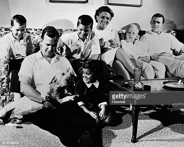 The Bush family at home George Bush and daughter Dorothy sit on the living room floor playing with a dog On sofa are Marvin Jeb Barbara Neil and...