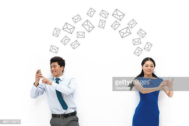 The business of young men and women holding a mobile phone to send text messages