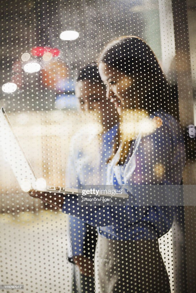 The business women through a window at night : Stock Photo