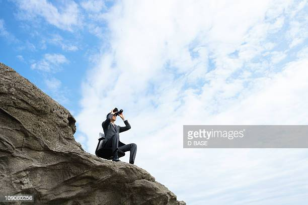 The businessman looking through telescope on cliff