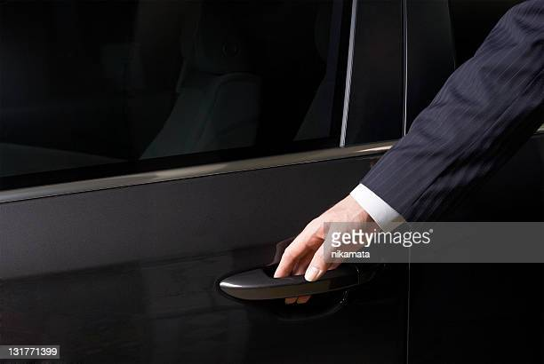 The businessman opens a door of the car