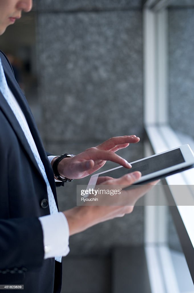 The businessman using a digital tablet : Stock Photo