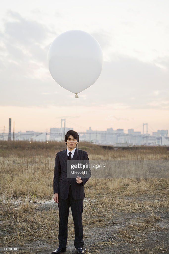 The businessman who stands with a balloon : Stock Photo