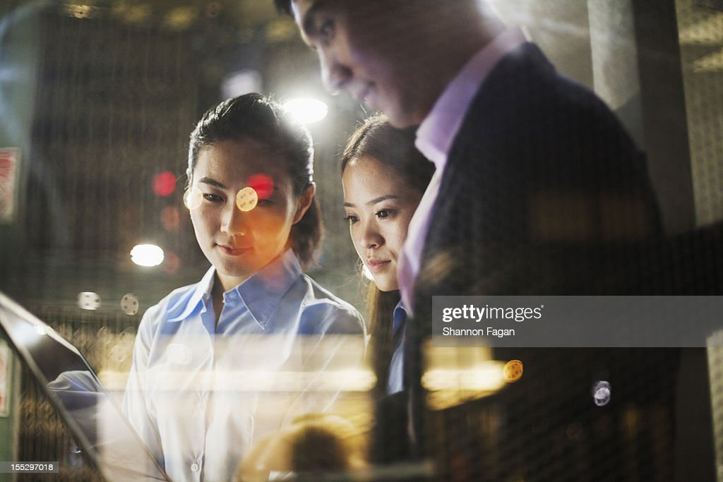 The businessmen through a window at night : Stock Photo