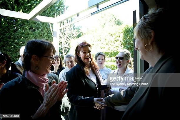 The buyer is congratulated in centre by the agent on right at the auction of 5 St Andrews St Balmain East 16 July 2005 SMH Picture by TAMARA DEAN