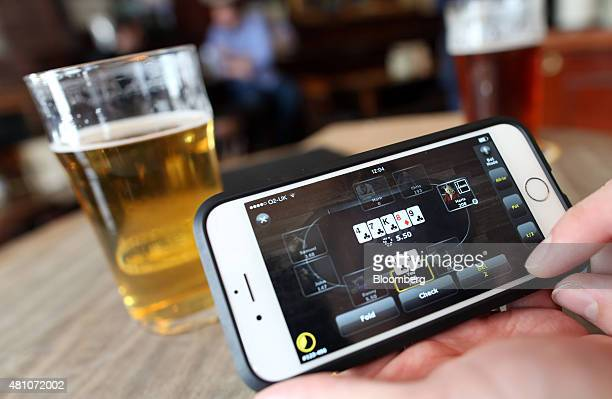 The Bwinparty Digital Entertainment Plc online poker app sit on an Apple Inc iPhone 6 smartphone beside a pint of beer in this arranged photograph...