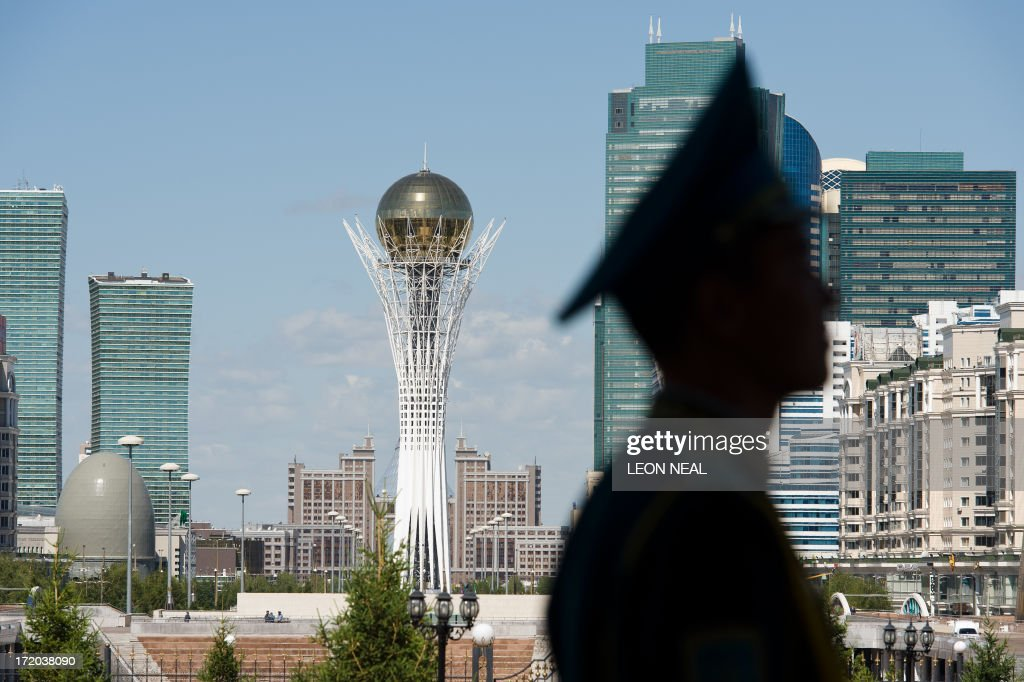 The Byterek tower is visible in the centre of Astana as a soldier stands guard outside the Presidential Palace in Astana, Kazakhstan on July 1, 2013. David Cameron arrived in Kazakhstan on June 30, 2013 on the first ever trip by a serving British prime minister, hoping to boost trade ties but also promising to raise human rights concerns.