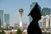 The Byterek tower is visible in the centre of Astana as a soldier stands guard outside the Presidential Palace in Astana Kazakhstan on July 1 2013...