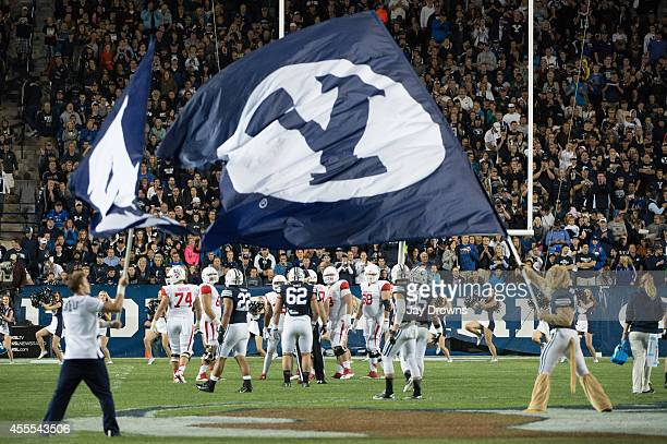 The BYU Cougars mascot and cheerleader waves a flag at midfield during a game against the Houston Cougars on September 11 2014 at LaVell Edwards...
