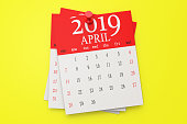 The calendar on a yellow background. Calendar papers in front of the yellow wall