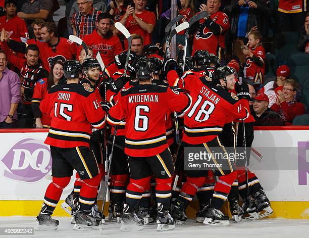 The Calgary Flames celebrate after a goal in OT against the Detroit Red Wings at Scotiabank Saddledome on October 23 2015 in Calgary Alberta Canada
