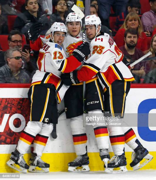 The Calgary Flames' Micheal Ferland celebrates his goal with Johnny Gaudreau and Sean Monahan during the second period against the Carolina...