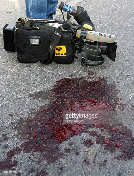 The camera of Reuters cameraman Fadel Shaana sits beside a pool of blood on the road after his car was hit by an Israeli missile on April 16 2008 in...