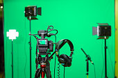 The camera on the tripod, led floodlight, headphones and a directional microphone on a green background. The chroma key. Green screen.