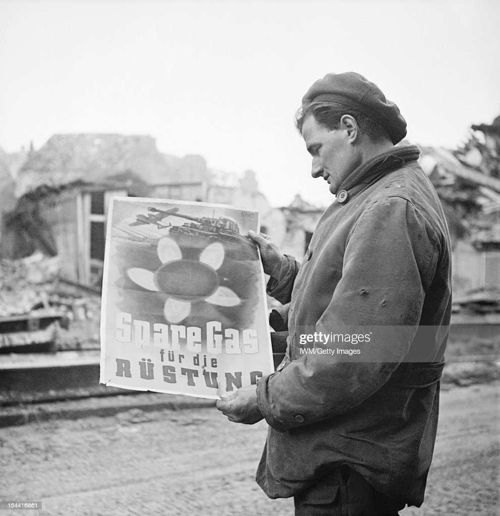 The Campaign In North West Europe 1944-45, A soldier standing in the ruins of Kleve, reading a German poster calling for civilians to conserve fuel supplies for the war effort, 13 February 1945.
