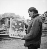 The Campaign In North West Europe 194445 A soldier standing in the ruins of Kleve reading a German poster calling for civilians to conserve fuel...