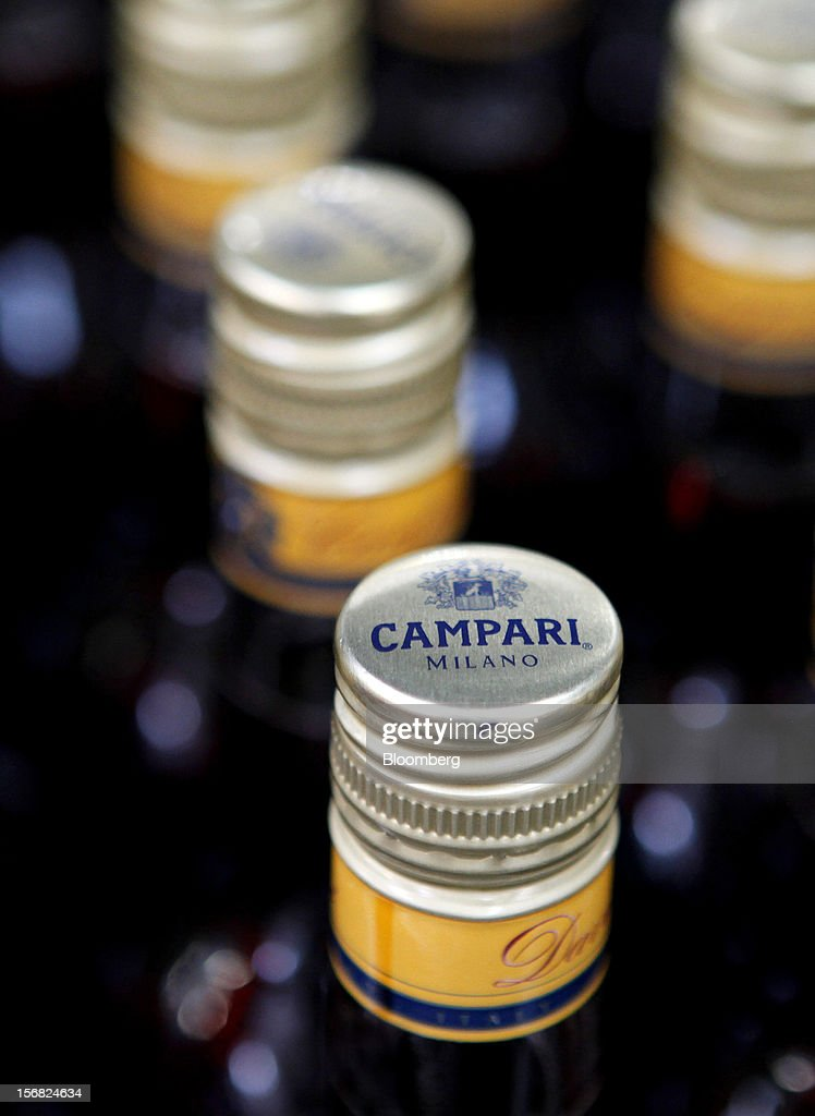 The Campari logo sits on the lid of a filled bottle of Campari as it travels along the production line at Davide Campari-Milano SpA's factory in Novi Ligure, Italy, on Wednesday, Nov. 21, 2012. Business conditions in Italy, where Campari gets almost a third of annual revenue, are likely to remain volatile in the fourth quarter and early next year, Chief Executive Officer Bob Kunze-Concewitz said. Photographer: Alessia Pierdomenico/Bloomberg via Getty Images