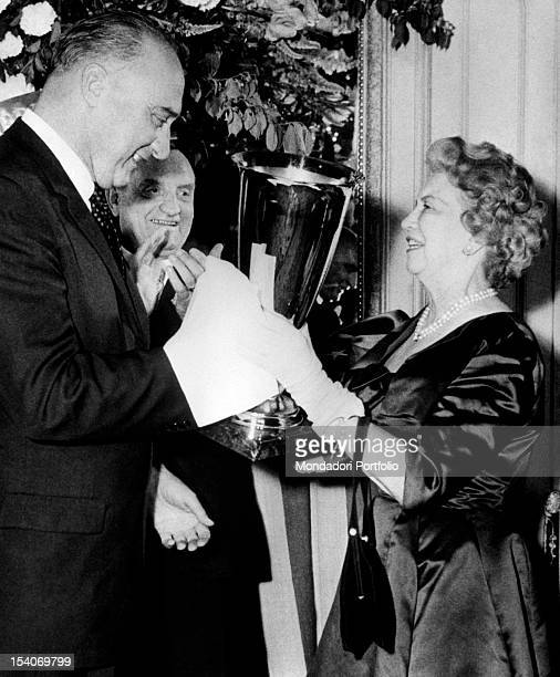 The Canadian businesswoman Elizabeth Arden receives from the French ambassador Bayens the Coupe du Bon Gout for creating the Memoire Cherie perfume...
