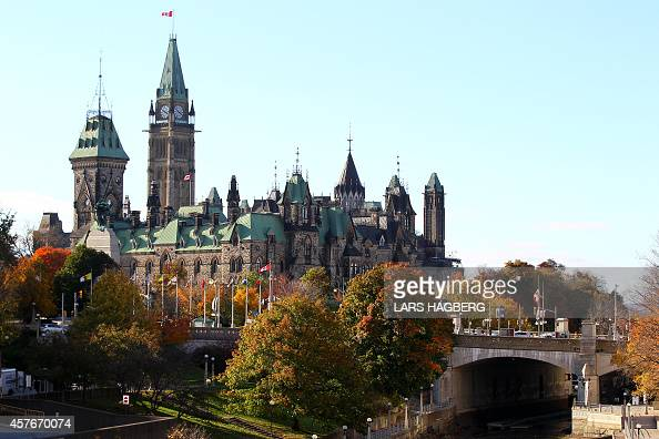 The Canadian flag flies over the Parliament hill in Ottawa Canada on October 22 2014 A gun man opened fire at the National War Memorial and killed an...