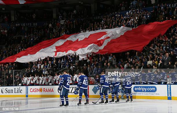 The Canadian flag is passed from hand to hand in the stands as Toronto Maple Leafs' Nikita Zaitsev Nazem Kadri Leo Komarov Morgan Rielly and Nikita...