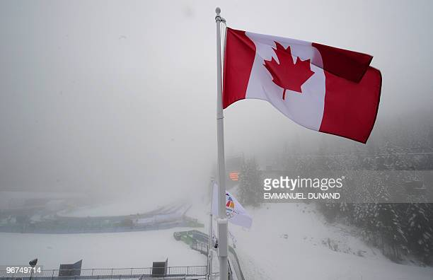 The Canadian flag is seen as rain showers replace snow flurries on February 16 2010 at the Whistler Creekside Alpine skiing venue of the Vancouver...