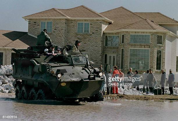 The Canadian Military in an armoured personel carrier drive away from a house that is flooding after dropping off people to sandbag because of high...