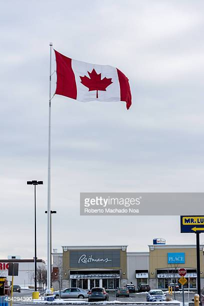 The Canadian National flag flying high on a tall flag post at a square in front of the Reitmans store with cloudy sky in the background The Canadian...