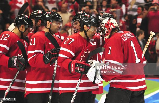 The Canadian team celebrate with their goalkeeper Roberto Luongo after beating Germany 82 in the Men's Ice Hockey playoff game between Canada and...