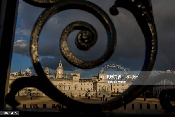 The capital's landmark Horseguards is seen through railings in St James's Park on 21st March 2017 in London England Horse Guards is a large Grade I...