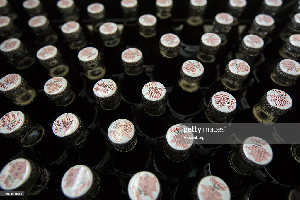 The caps of Coke bottles are seen as they move along the production line at the Lanitis Bros Ltd. bottling plant, part of the Coca-Cola Hellenic Group, in Nicosia, Cyprus, on Tuesday, June 10, 2014. Zug, Switzerland-based Coca-Cola Hellenic Bottling Co., which distributes Coca-Cola products in countries including Russia, wants to move away from using imported sugar for its Russian operations by 2015. Photographer: Andrew Caballero-Reynolds/Bloomberg via Getty Images