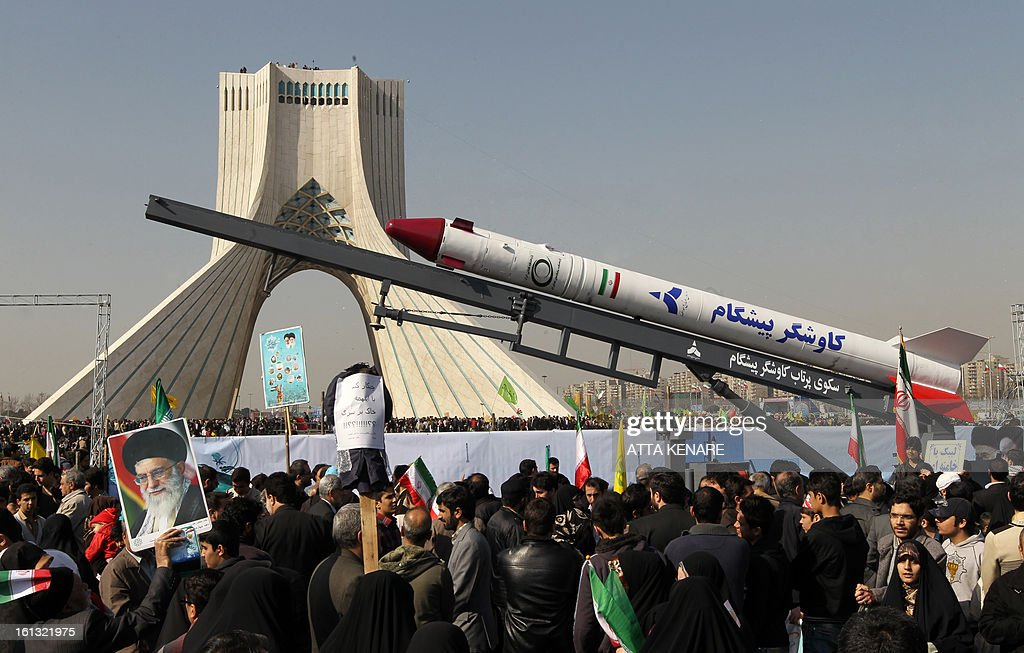 The capsule that was sent into space containing a live monkey in January is displayed during a rally in Tehran's Azadi Square (Freedom Square) to mark the 34th anniversary of the Islamic revolution on February 10, 2013. Hundreds of thousands of people marched in Tehran and other cities chanting 'Death to America' and 'Death to Israel' as Iran celebrated the anniversary of the ousting of the US-backed shah. AFP PHOTO / ATTA KENARE