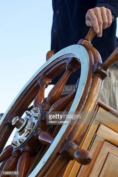 The captain keeps his hand on ship's wheel on board the sailing yacht