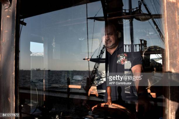The captain of the boatbar 'Arabella' Kostas Malliaros is seen behind a window during a tour in the Thermaikos gulf in Thessaloniki on August 31 2017...
