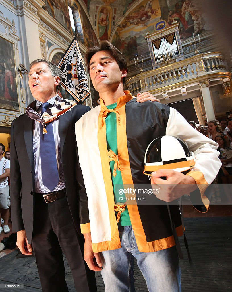 The Captain of the Contrada della Lupa, Guido Burrini, holds jockey Jonatan Bartoletti ,also known as Scompiglio after the Benediction of the horse and rider before the annual Palio dell'Assunta horse-race on August 16, 2013 in Siena, Italy. The Palio races in Siena, in which riders representing city districts compete,and takes place twice a year in the summer in a tradition that dates back to 1656.