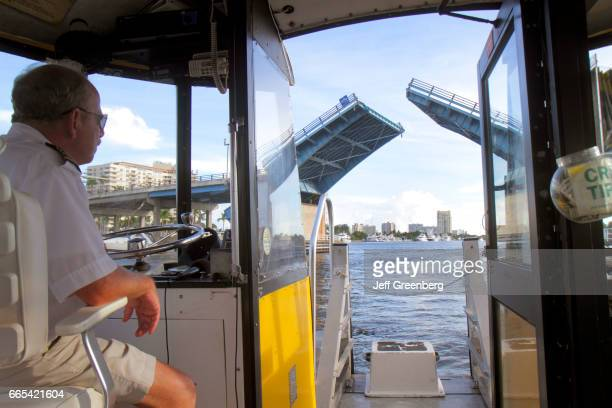The captain on the water taxi waiting to go under the East Las Olas Boulevard Bridge