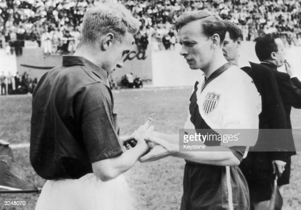 The captains of England and USA Billy Wright and Ed McIlvenny exchange souvenirs at the start of their match on June 29 1950 in Belo Horizonte Brazil...