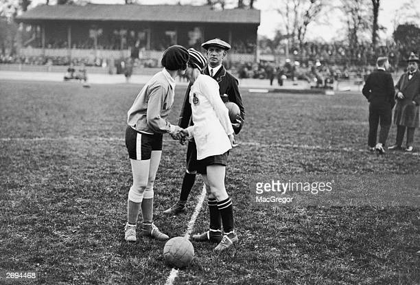 The captains of the French and English Ladies football teams Carmen Pomies and Florrie Redford having a handshake and a peck on the cheek before the...