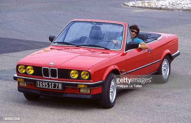 The car driver Cyril Neveu tests a convertible BMW 325 in 1986 le pilote automobile Cyril Neveu essai un cabriolet BMW 325 I en 1986