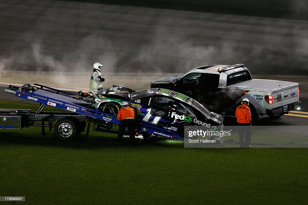 The car of Denny Hamlin, driver of the #11 FedEx Ground Toyota, is towed after being involved in an incident during the NASCAR Sprint Cup Series Coke Zero 400 at Daytona International Speedway on July 6, 2013 in Daytona Beach, Florida.