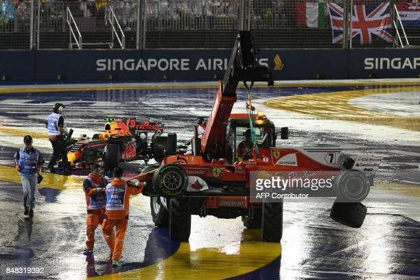 The car of Ferrari's Finnish driver Kimi Raikkonen is removed after a crash with Red Bull's Dutch driver Max Verstappen during the Formula One...