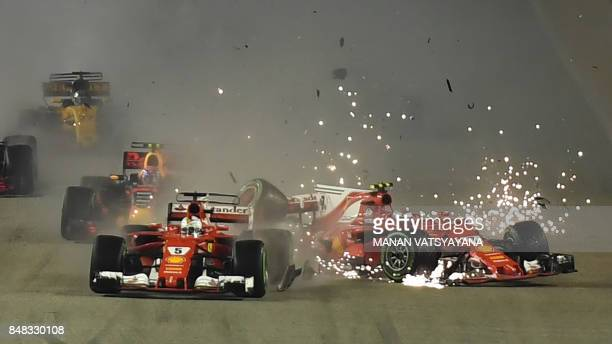TOPSHOT The car of Ferrari's Finnish driver Kimi Raikkonen is seen after a crash as Ferrari's German driver Sebastian Vettel leads during the Formula...