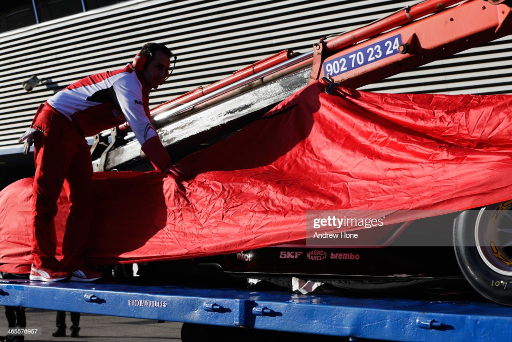 The car of Kimi Raikkonen of Finland and Ferrari returns to the pitlane on a flatbed truck after encountering a problem during day one of Formula One Winter Testing at the Circuito de Jerez on January 28, 2014 in Jerez de la Frontera, Spain.