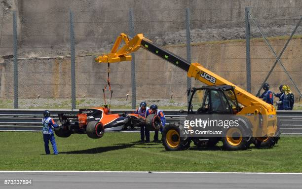 The car of McLaren's Belgian driver Stoffel Vandoorne is removed from the course after he was forces to abandon right after the start of the...