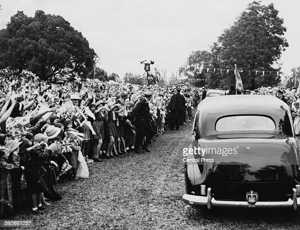 The car of Queen Elizabeth II driving past crowds of children who are waving Union Jack flags as the car makes its way to Carrington Park Casino New...