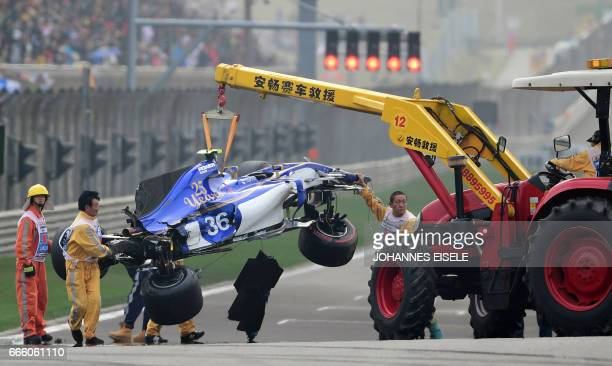 The car of Sauber's Italian driver Antonio Giovinazzi is removed from the track after a crash during the qualifying session for the Formula One...