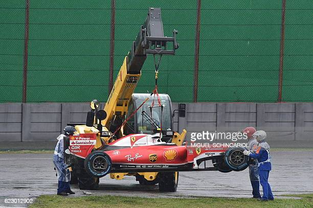 The car of Scuderia Ferrari's Finnish driver Kimi Raikkonen is removed from the track after he crashed and the race was stopped during the Brazilian...