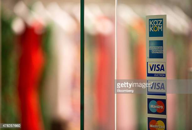 The card payment logos of Kazkommertsbank JSC top Visa Inc Maestro and Mastercard Inc sit on a store window at the Esentai luxury shopping mall in...