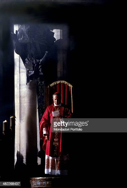 The Cardinal Carlo Maria Martini Archbishop of Milan wearing the typical purple religious vestment and cap reads silently a prayer from a booklet in...